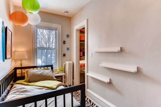 We've made this very small room a functional kids bedroom by utilizing the vertical space. We added low profile shelves/book ledges on the wall and a built-in desk and shelving in the closet for storage. I love the elfa closet systems we installed from the Container Store.