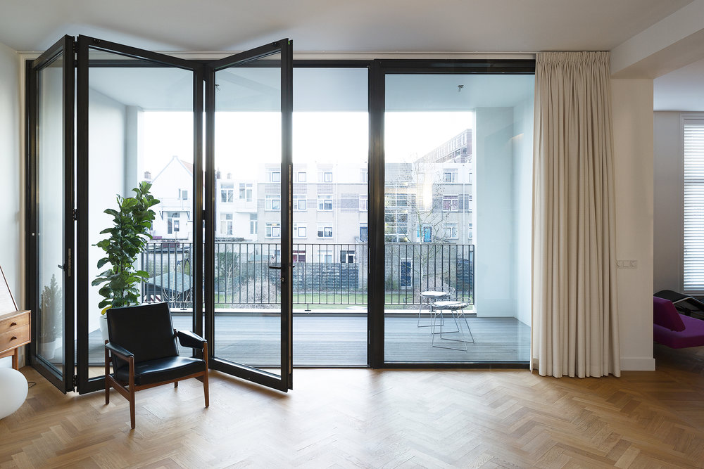 the large sliding doors connecting the living room with the french balcony