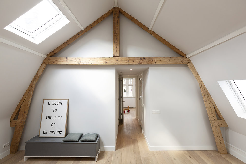 the large attic has a play area for the kids with roof lights for natural lighting. The structure of the roof is left visible.