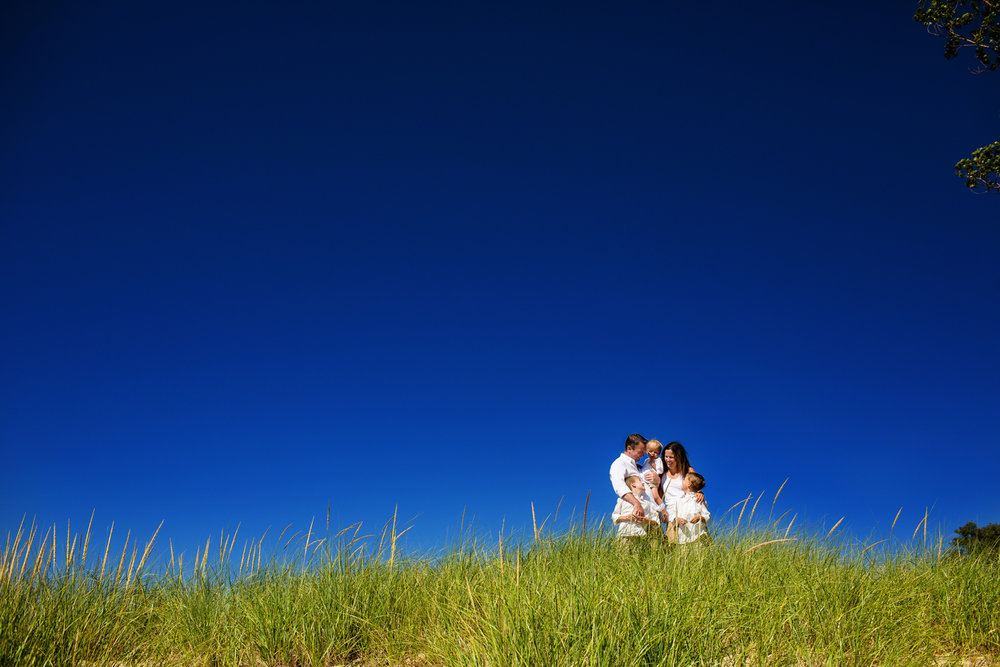family portrait in beach grass with blue sky