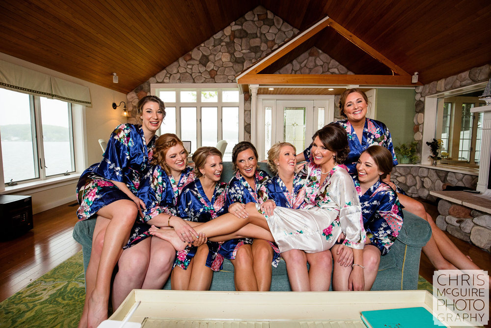 bride with bridesmaids in robes laughing