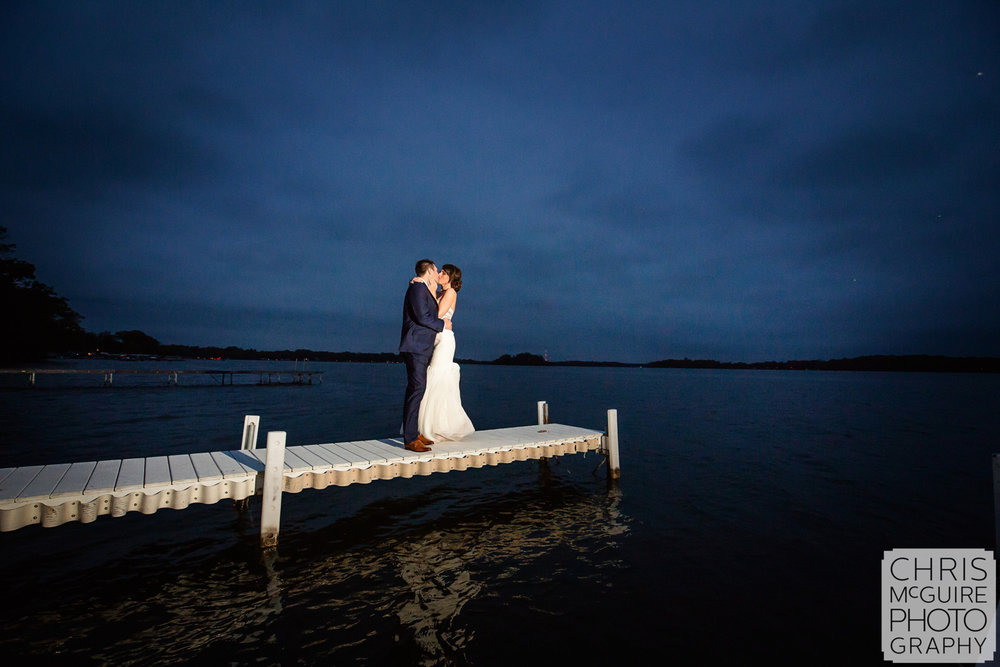 bride groom kissing on dock by lake at dusk