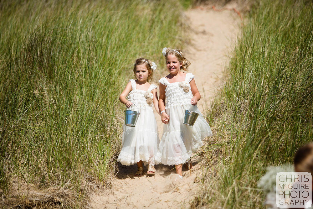 flower girls walking through beach grass