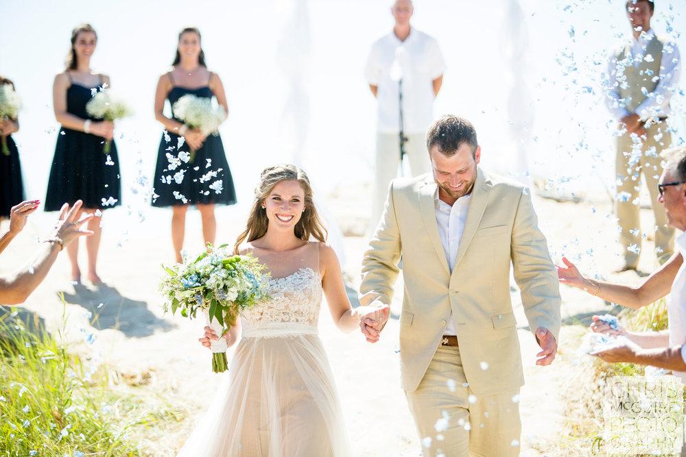 bride groom petal throwing at beach wedding ceremony