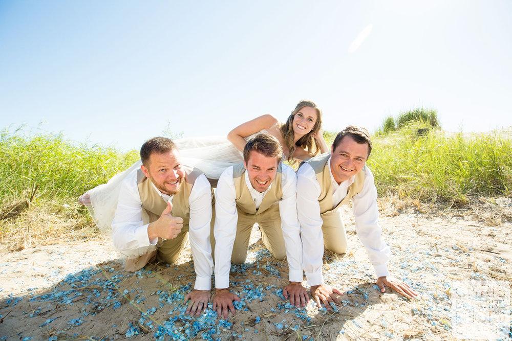bride on backs of groomsmen
