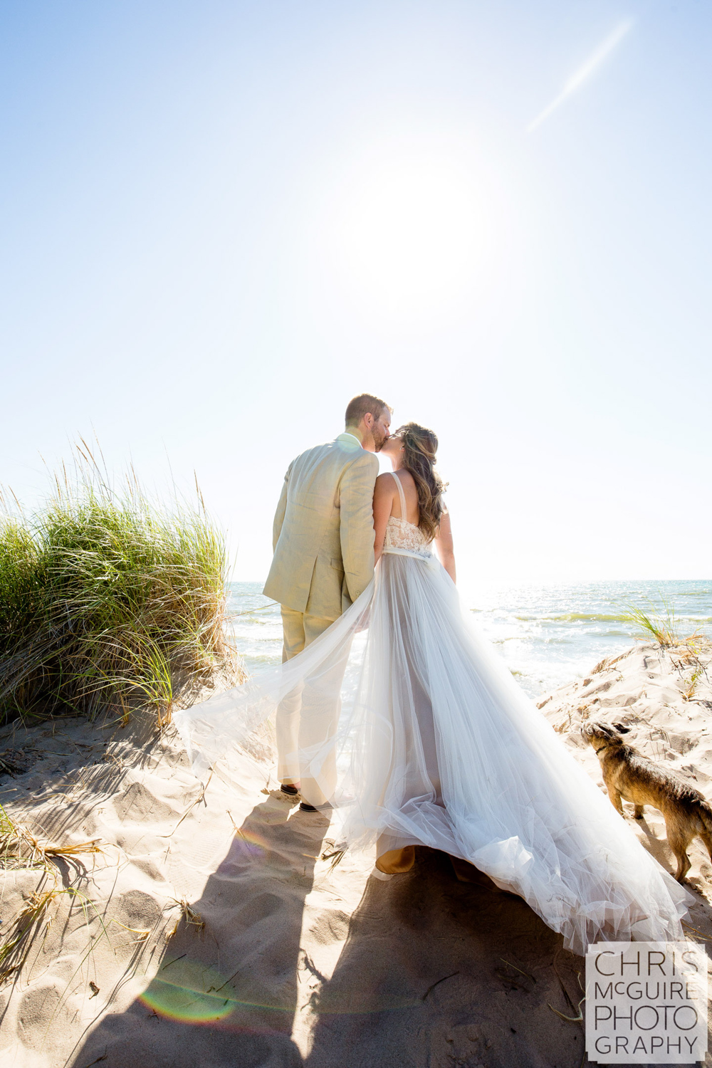 bride groom kissing in front of lake michigan