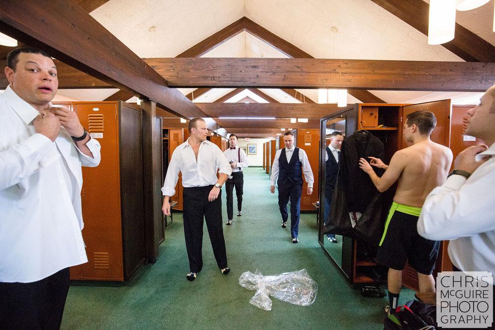 groom and groomsmen getting dressed in locker room