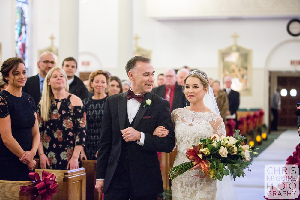father smiles at bride walking down aisle at wedding