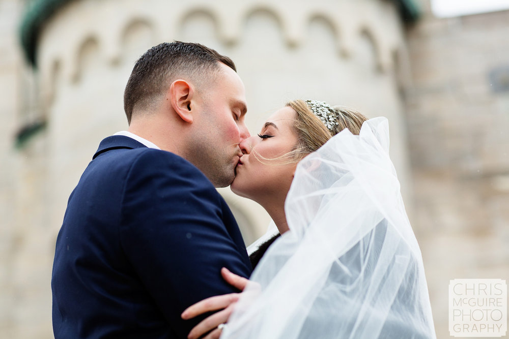 bride groom kissing in front of church