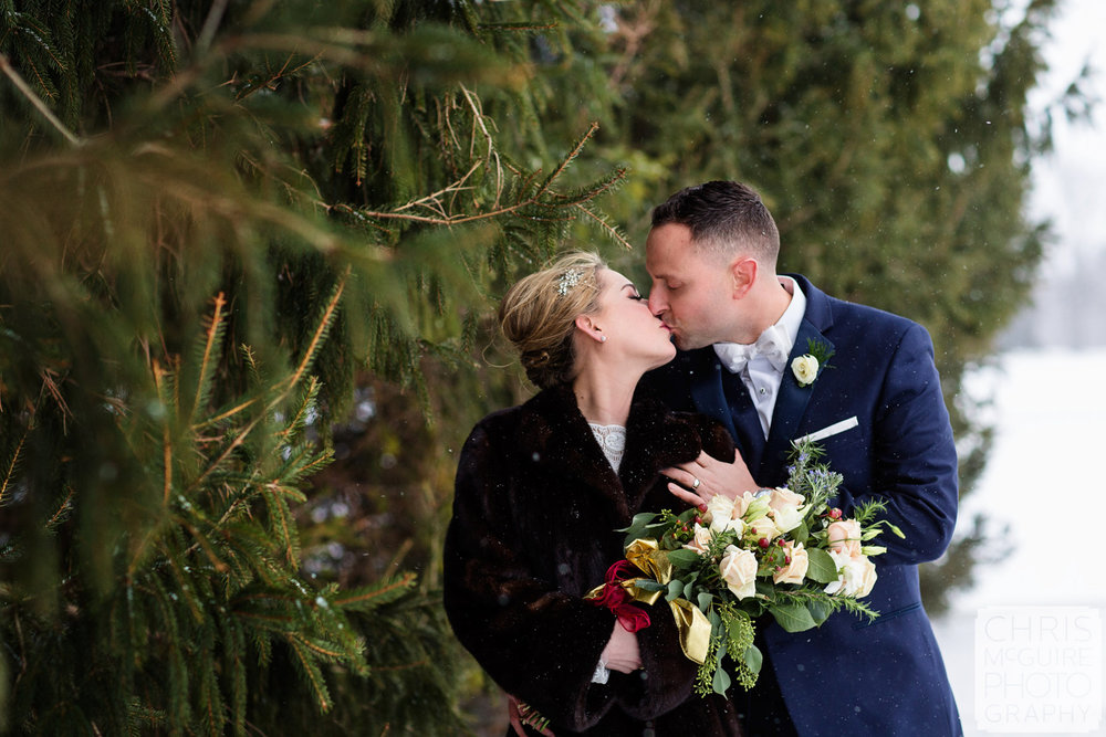 bride groom kissing in snow evergreen trees