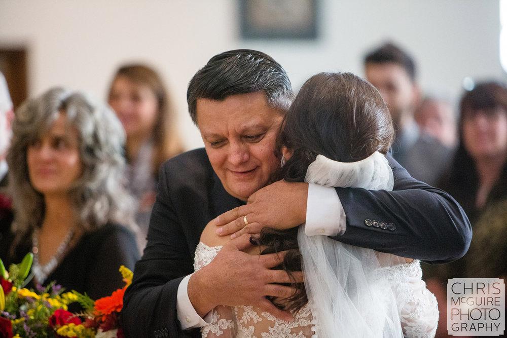 father hugs bride at wedding