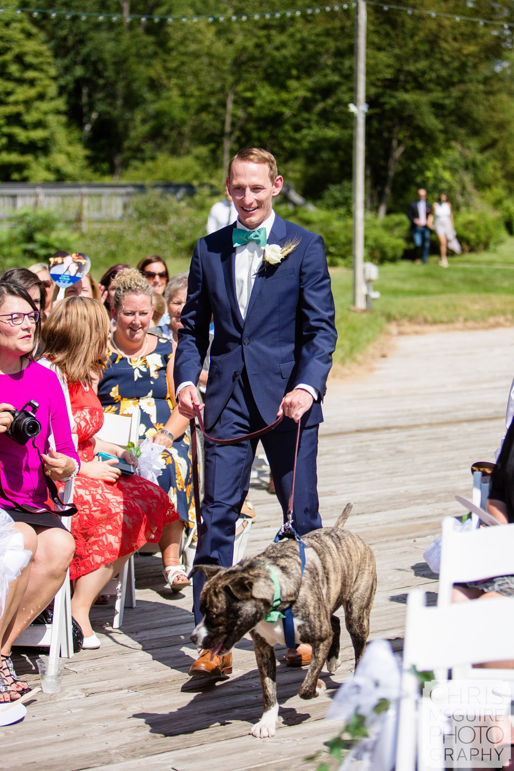 groom with dog walking down aisle