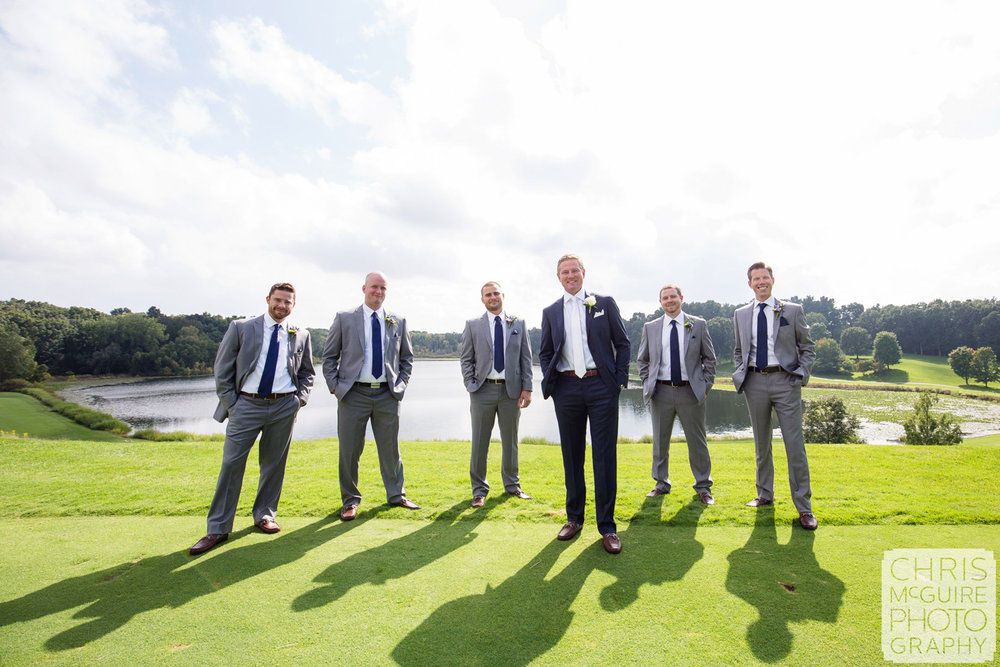 groom and groomsmen on golf course with lake