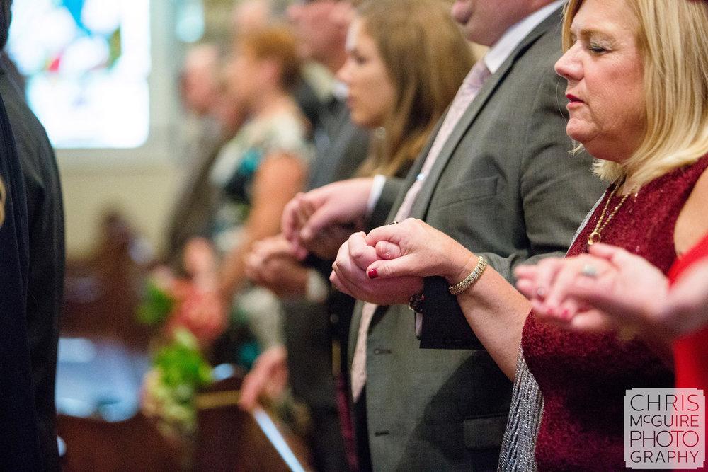 guests praying at catholic wedding