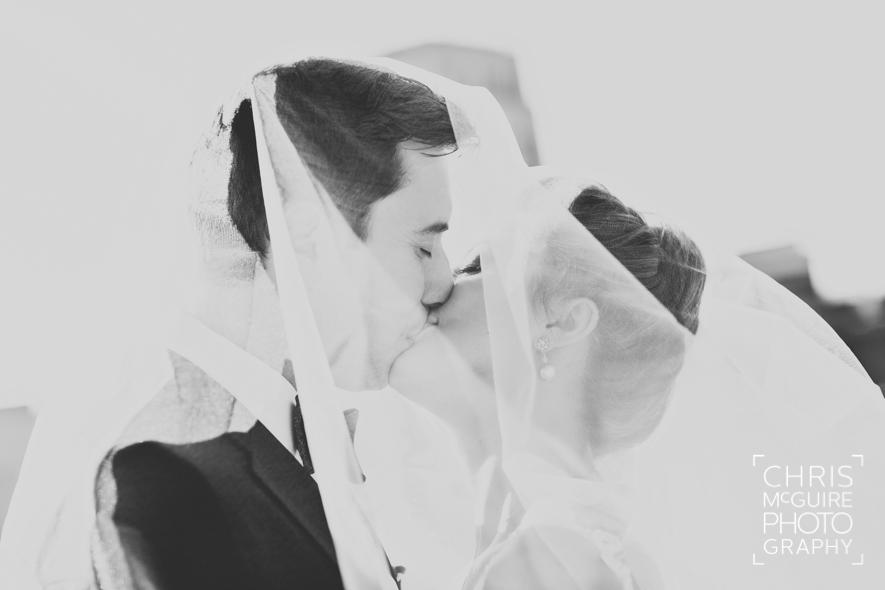 bride groom kissing under veil