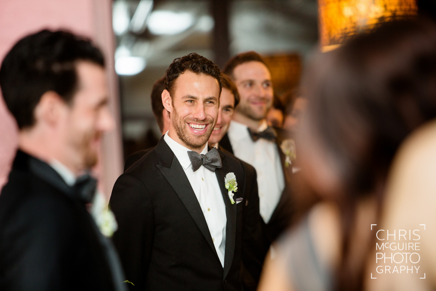 groomsman laughing during wedding ceremony