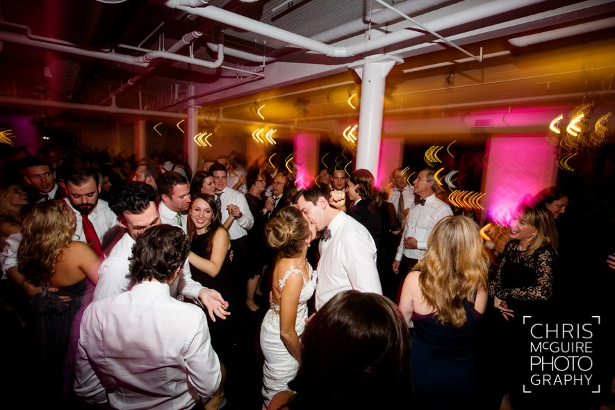 bride groom kissing on dancefloor at loft wedding