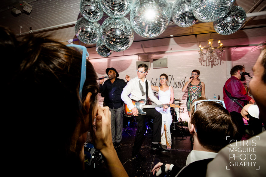 groom playing guitar with live band at wedding reception