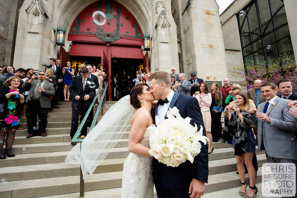 bride groom kiss outside church surrounded by guests peoria