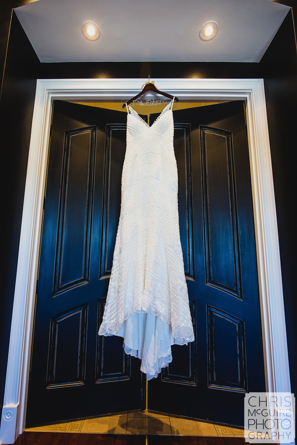 wedding dress hanging on black door