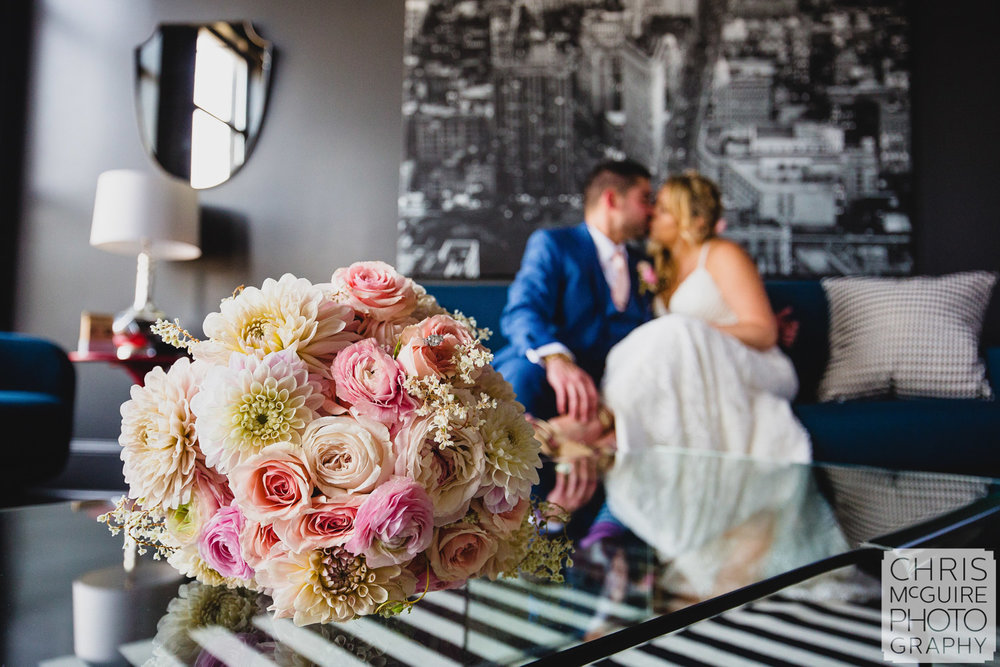bride groom kissing behind bouquet