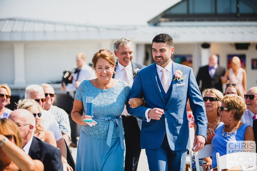 groom walking down aisle with mother