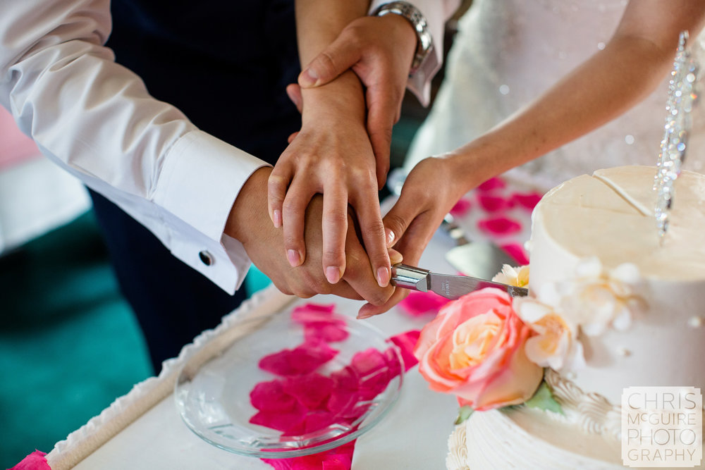 bride groom hands cutting wedding cake
