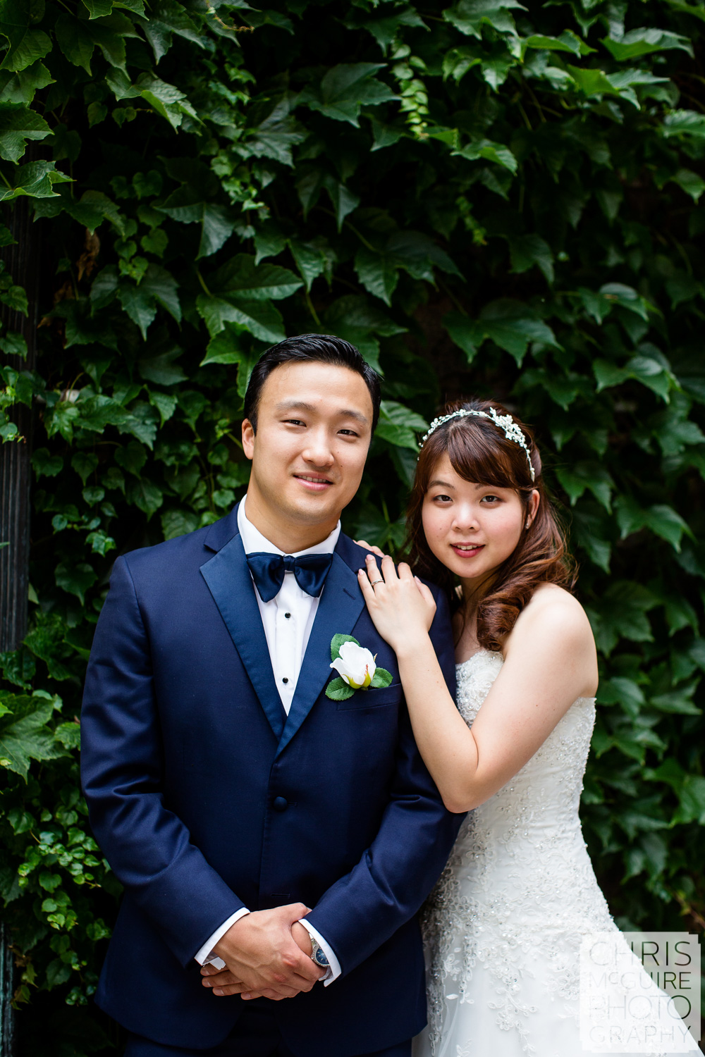 bride and groom with ivy wall