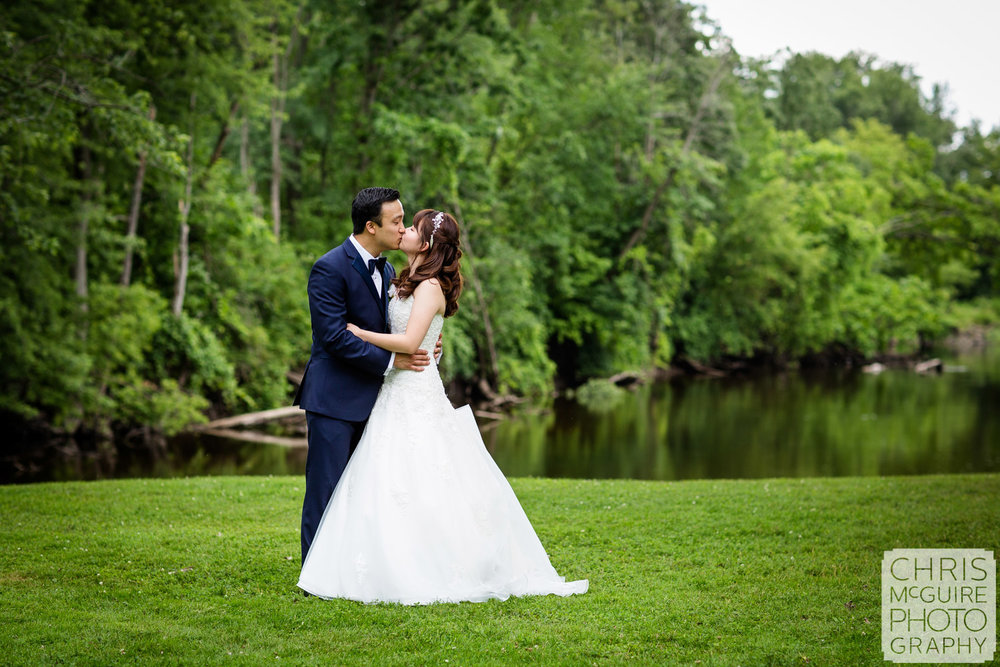 bride groom kissing in front of river