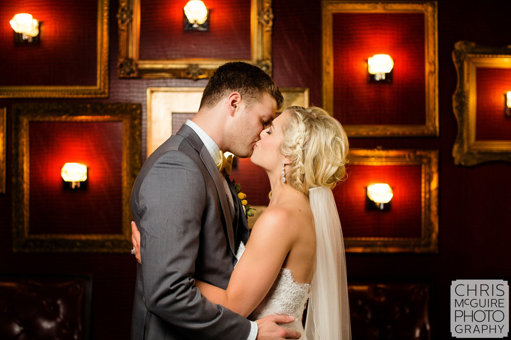 bride groom kiss red wall
