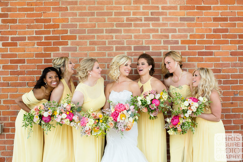 bride bridesmaids with bouquets brick wall
