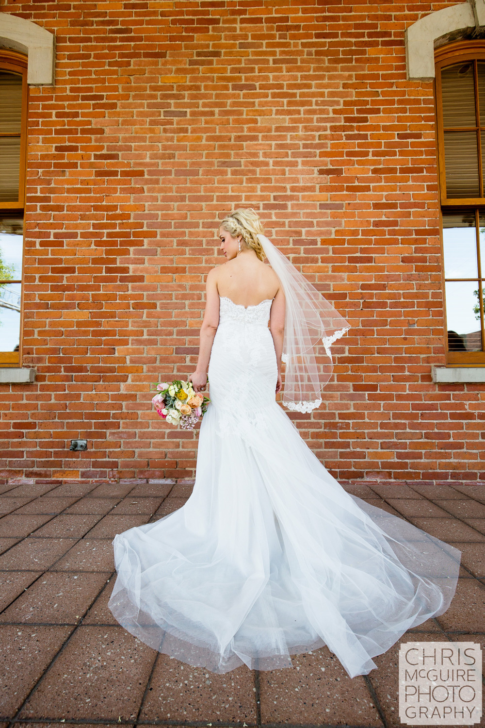 bride back of dress brick wall