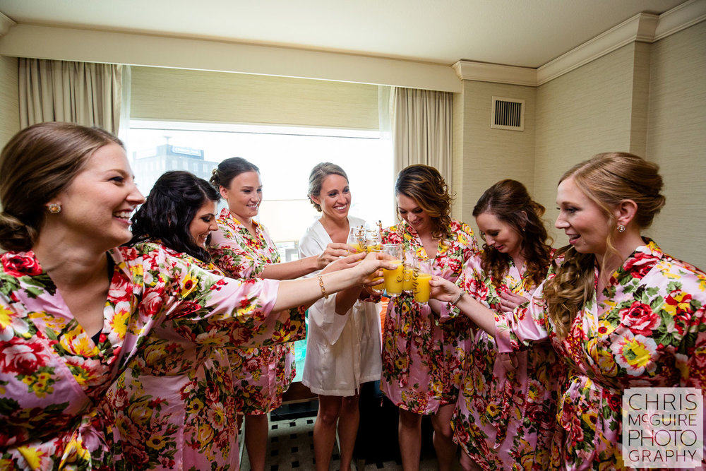 bride and bridesmaid toast in robes