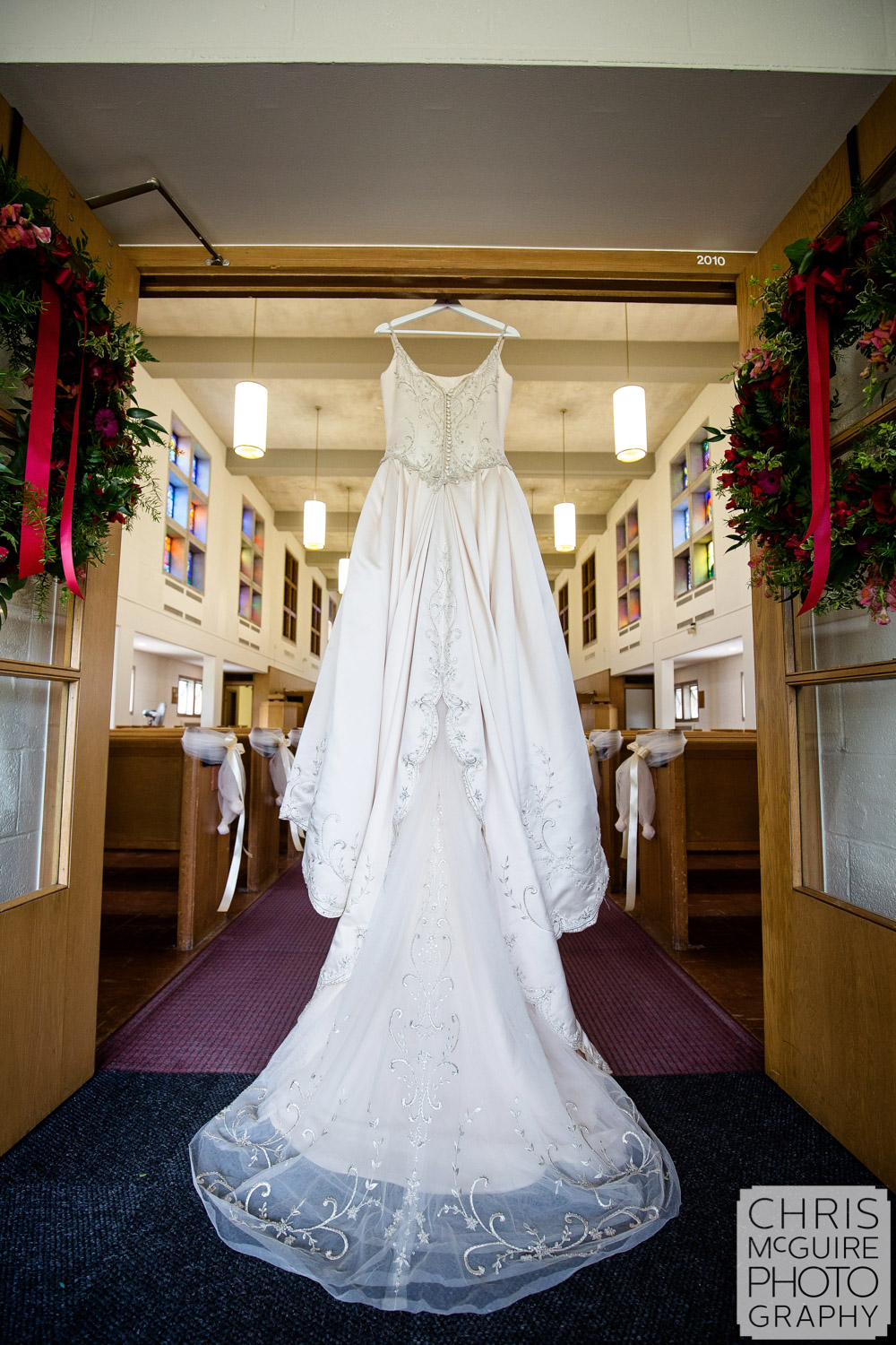 wedding dress hanging with wreathes