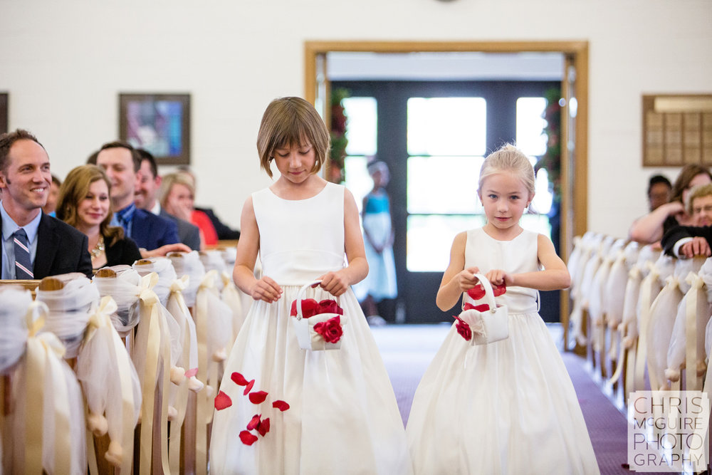 flower girls drop red petals at wedding