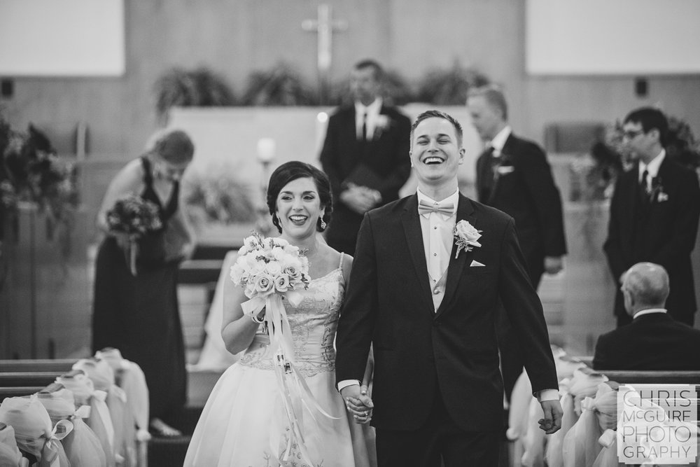 bride groom laugh as they walk down aisle after wedding