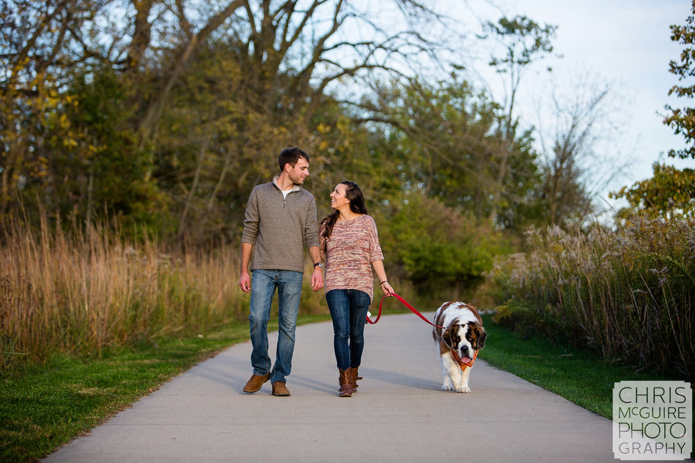 couple walking with dog at meadowbrook park in champaign urbana