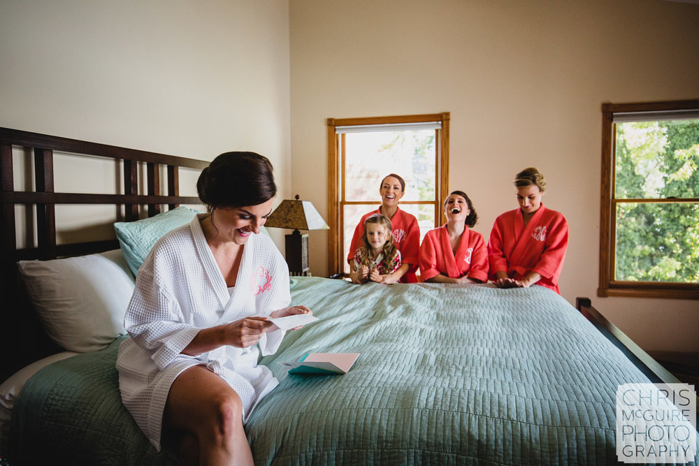 bride reading letter bridesmaids laughing