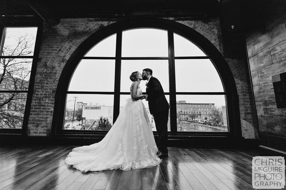 bride groom kissing in front of window