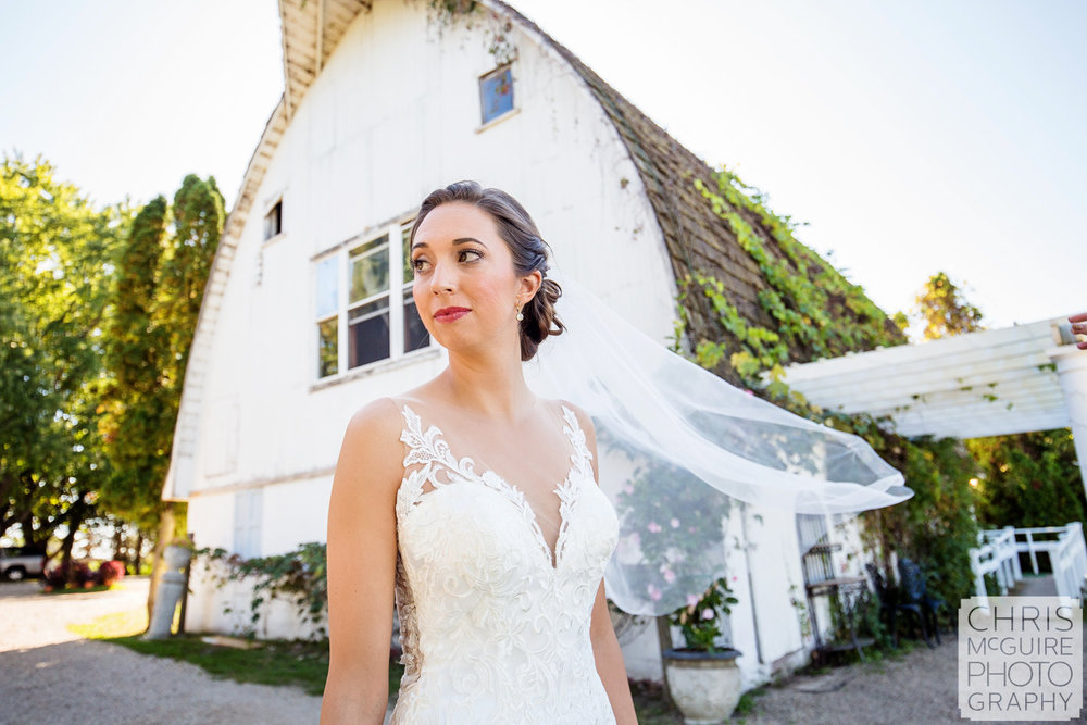 bride with veil in front of white barn