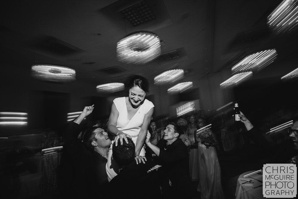 bride laughs as borther pick her up