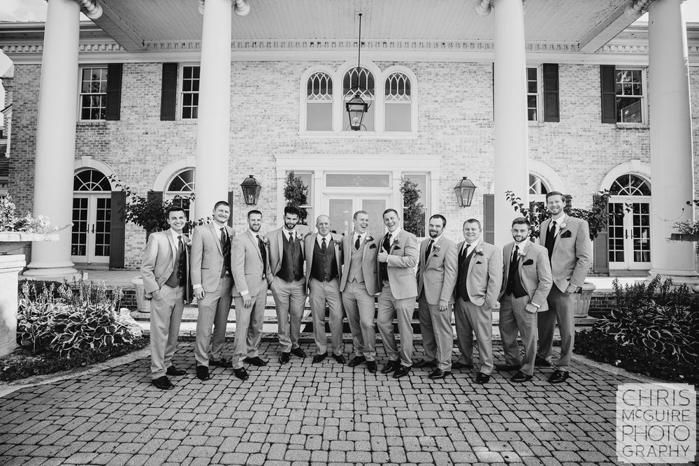 groom laughs with groomsmen midwest wedding