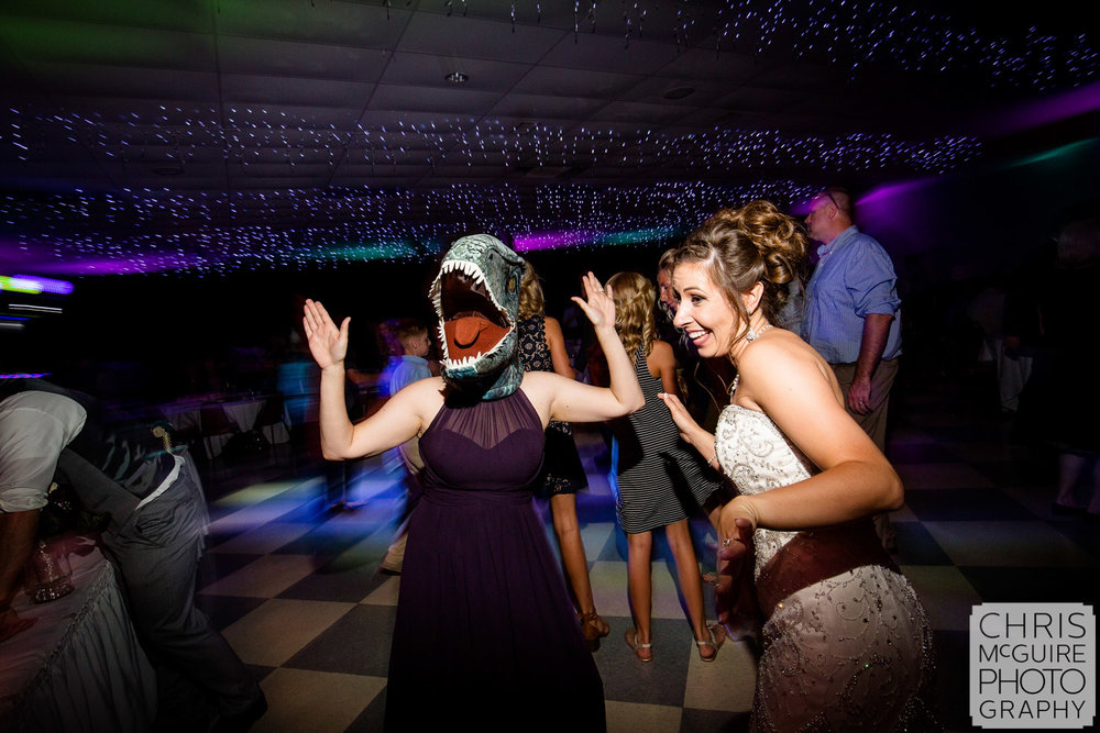 dinosaur mask and bride dancing at wedding reception