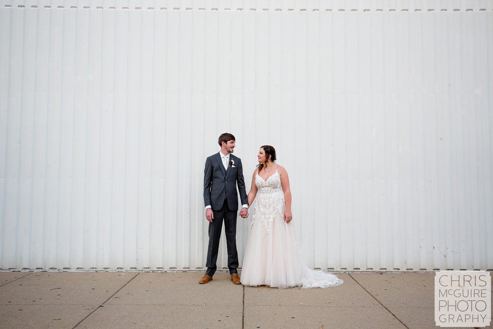 Bride and groom with white wall in Peoria IL