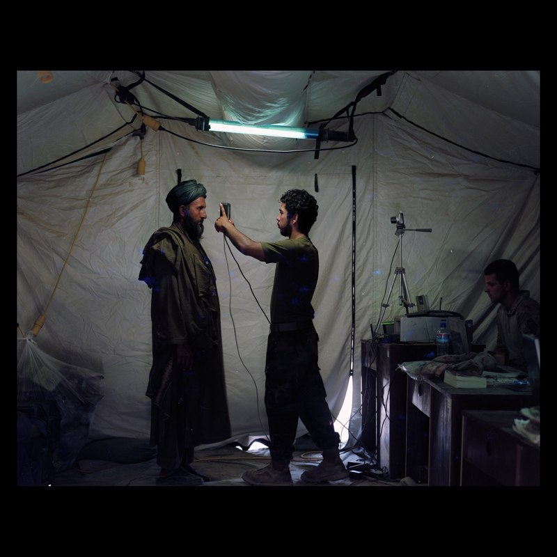 Afghan linguist working for US Marine Civilian Affairs unit doing a retinal scan of a Marja villager who has come to pick up bags of wheat. The villagers are given a retinal scan, photographed and their fingerprints are entered into a national database used to identify criminals.