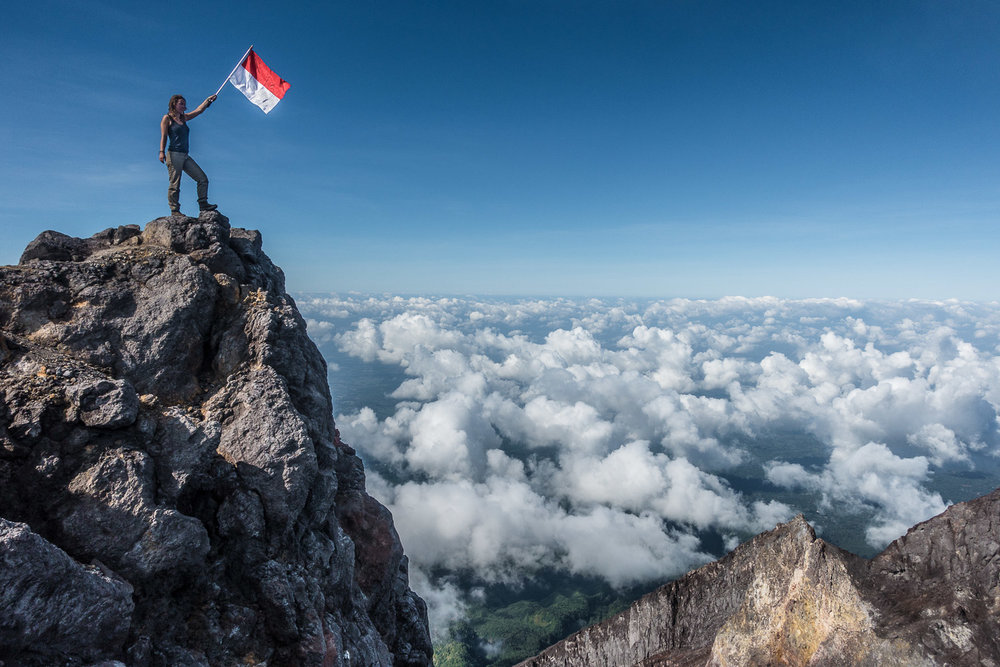 Eva waving the Indonesian flag on the summit of Merapi