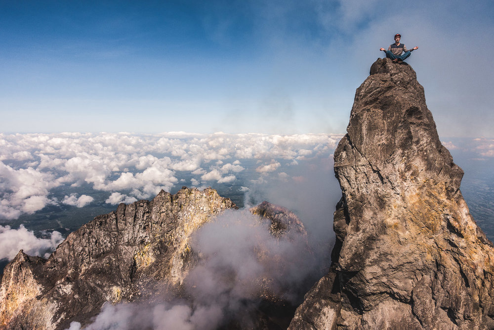 Trying to calm down on the summit pillar of Merapi with some meditation