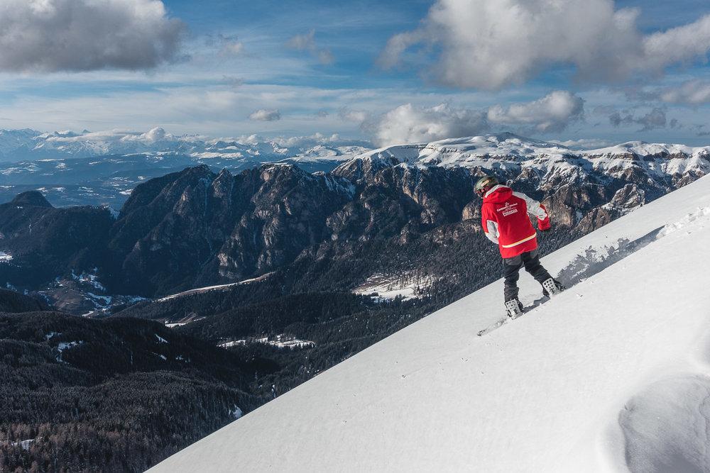 Ein Snowboarder zieht eine neue Linie im Tiefschnee