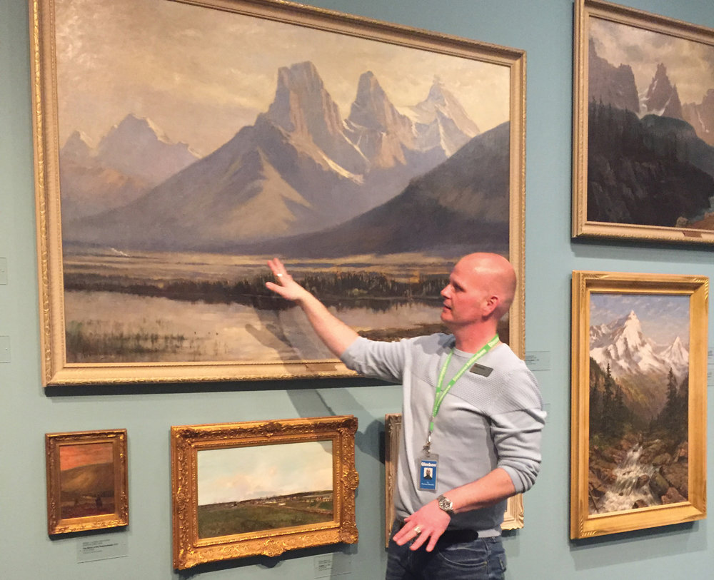 Glenbow educator Ty Larner points out some familiar landscapes to evoke memories during a dementia-friendly guided gallery tour. Photo courtesy Glenbow Museum.