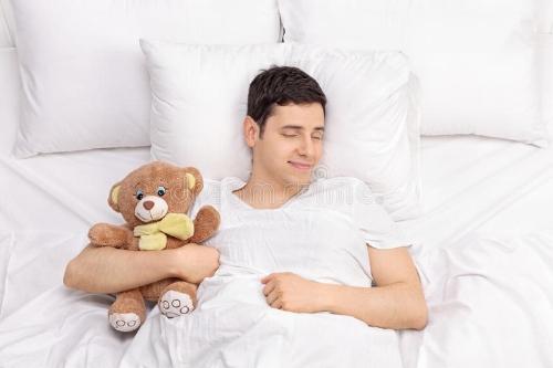 joyful-guy-sleeping-teddy-bear-childish-peacefully-comfortable-bed-74050303.jpg